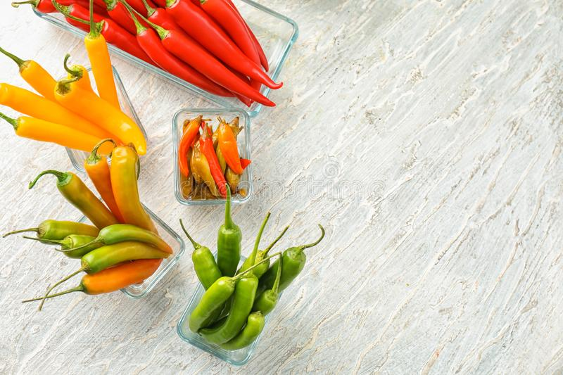 Glass bowls with fresh and canned chili peppers on light background stock photography