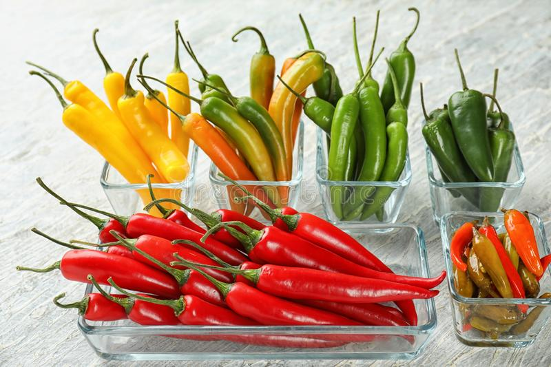 Glass bowls with fresh and canned chili peppers on light background royalty free stock photos
