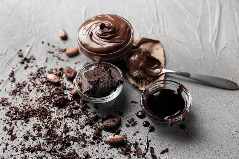 Glass bowls with molten chocolate and syrup on table royalty free stock image