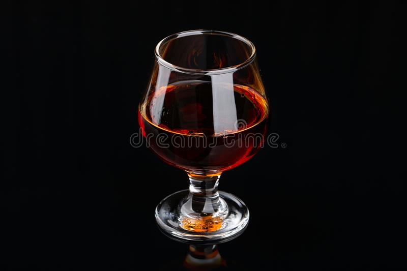 Glass of brandy on a black background stock images