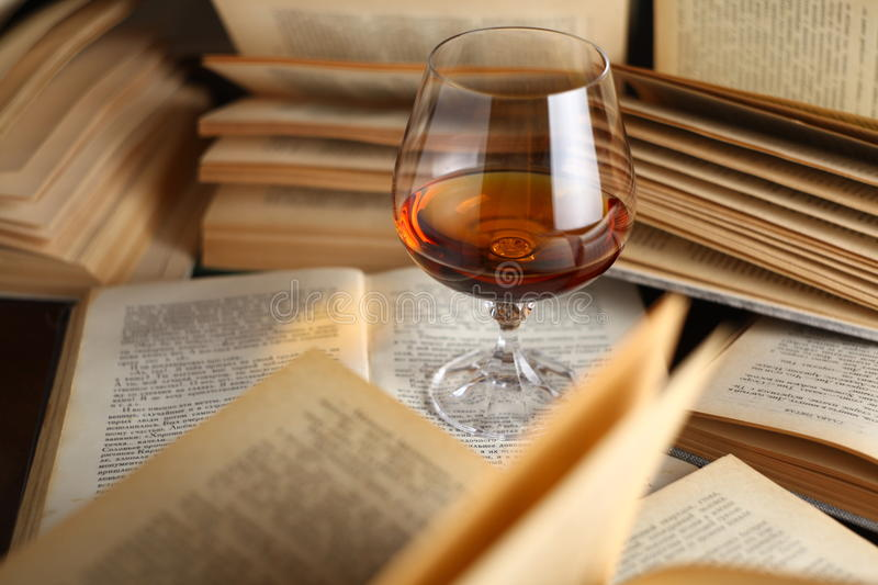 Glass of brandy on books royalty free stock image
