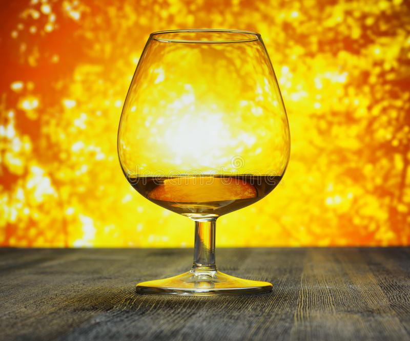 Glass of brandy on evening sky background royalty free stock images