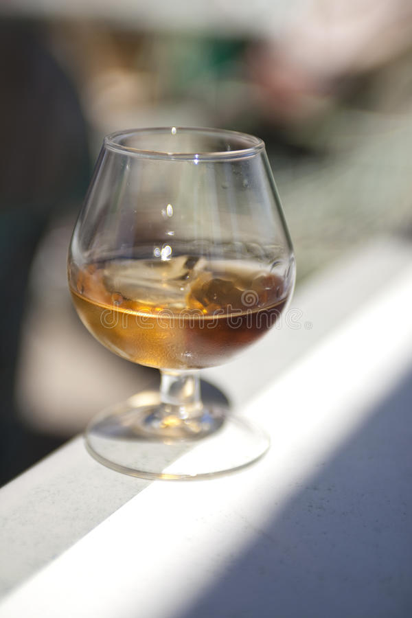 Glass of brandy with ice stock photo