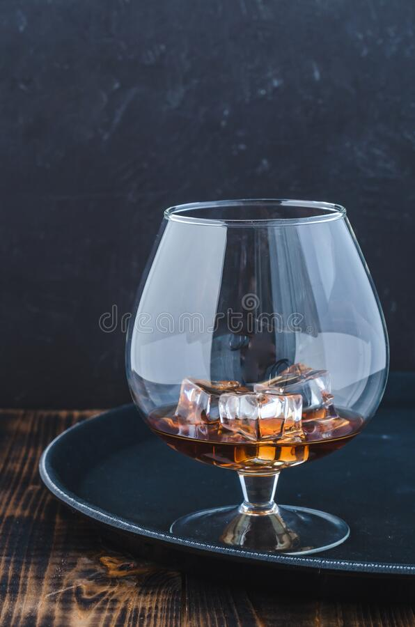 Glass of brandy with ice cubes/Glass of brandy with ice cubes on a black tray royalty free stock images