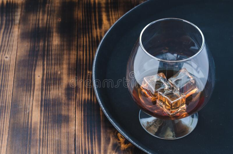 Glass of brandy with ice cubes/Glass of brandy with ice cubes on a black tray. Top view and copyspace royalty free stock photo