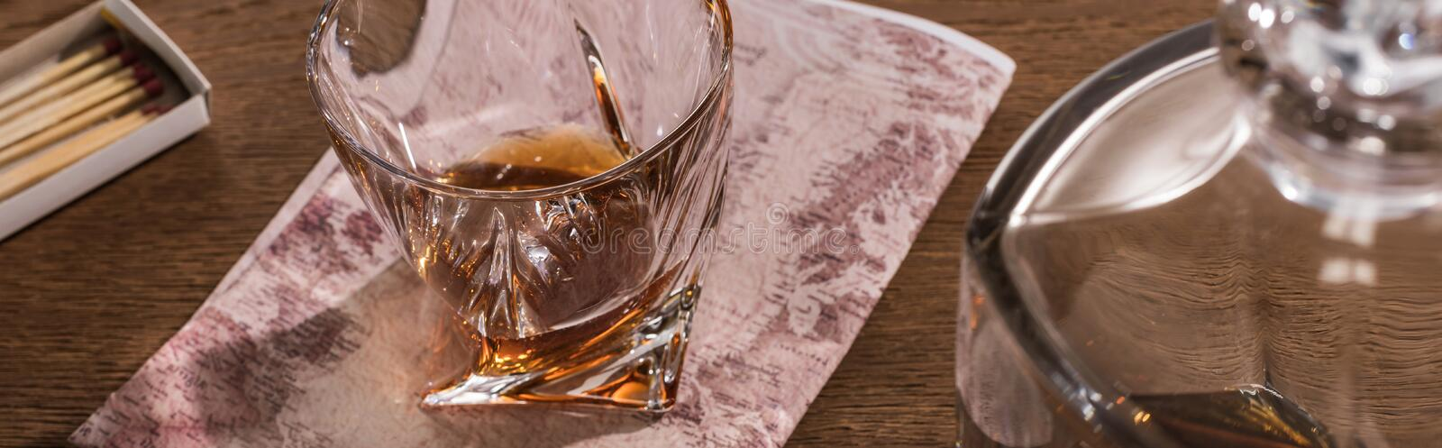 Glass of brandy on map with decanter and matches on wooden table, panoramic shot stock image