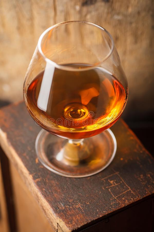 Glass of brandy near a barrel stock photo