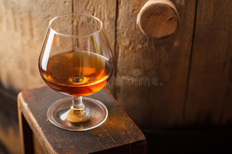Glass of brandy near a barrel stock photography