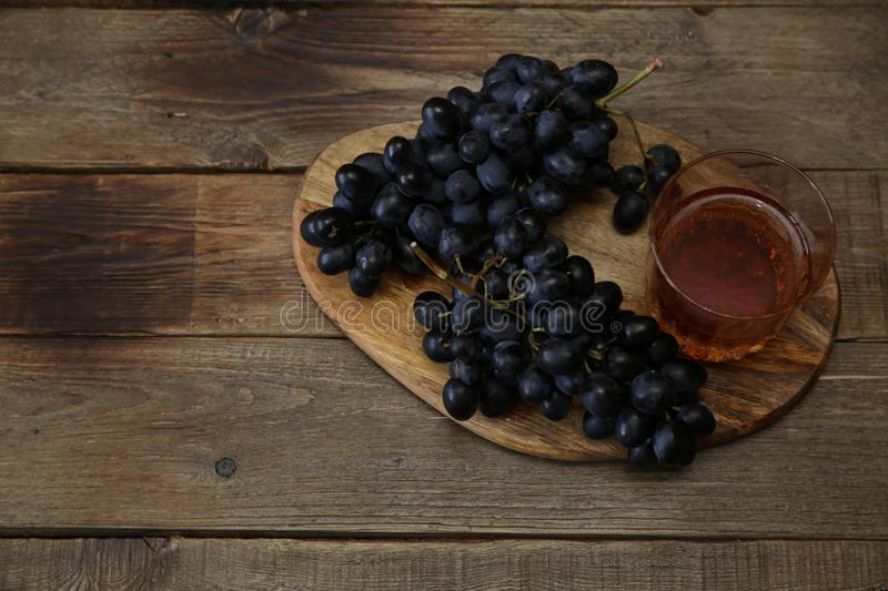Glass of brandy or wine and a juicy bunch of black grapes on a wooden rustic table. Top view. Flat lay. With copy space for text. stock photography