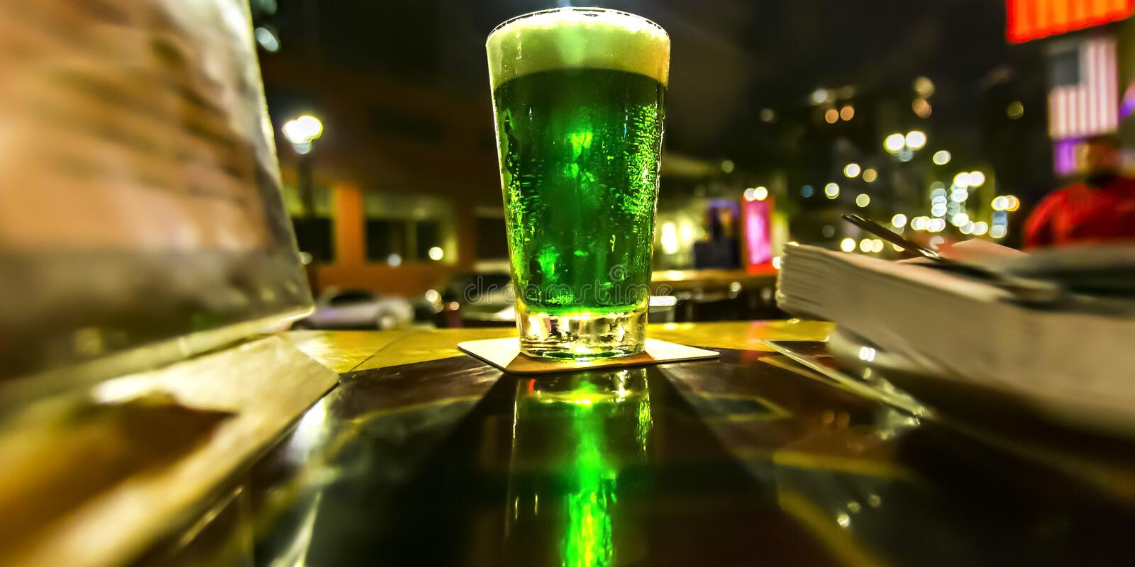 Glass with bright green liquid on a table at night stock photo
