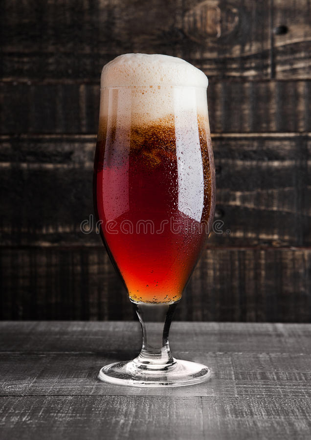 Glass of brown ale beer with foam on wood stock photos