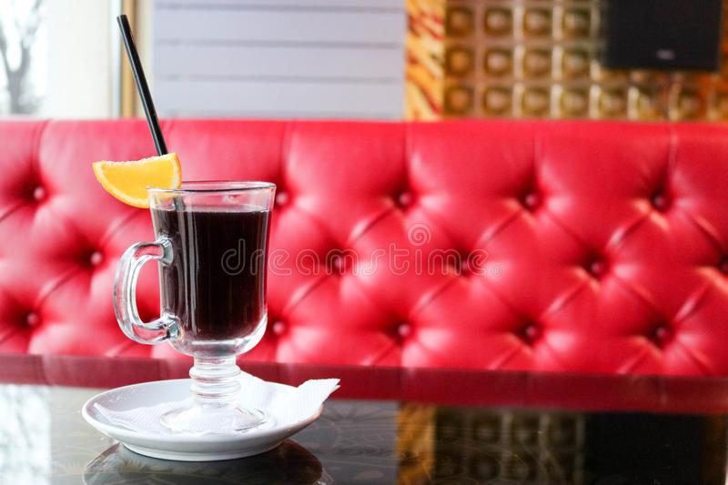 Glass with brown, tasty, hot, fragrant, alcoholic mulled wine on a table in a cafe in the evening on the background of a red leath. A glass glass with brown stock photo