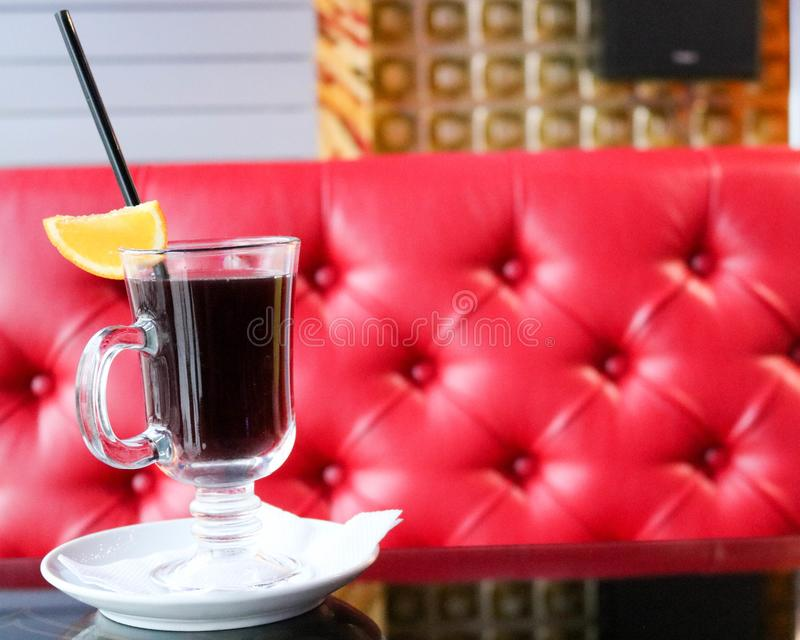 Glass with brown, tasty, hot, fragrant, alcoholic mulled wine on a table in a cafe in the evening on the background of a red leath. A glass glass with brown royalty free stock image