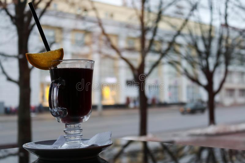 A glass glass with brown, tasty, hot, fragrant, alcoholic mulled wine on a table in a cafe in the evening. On the background of a red leather sofa royalty free stock photography