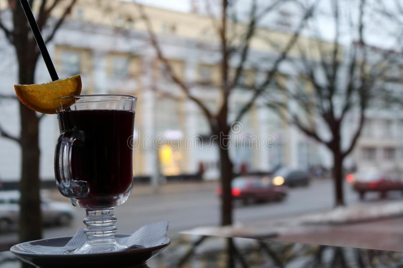 A glass glass with brown, tasty, hot, fragrant, alcoholic, warm mulled wine on a table in a cafe in the evening against a window. In the evening royalty free stock photography