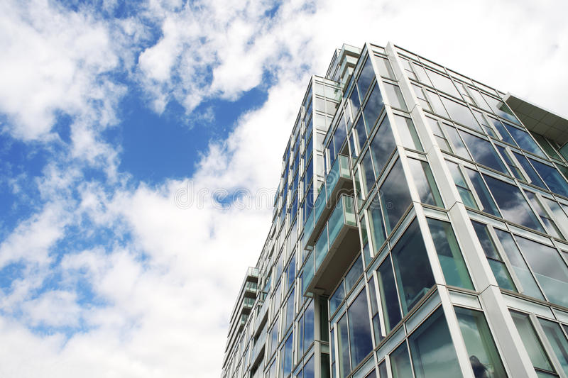 Glass building. Glass apartment building with reflective clouds and blue sky royalty free stock photos
