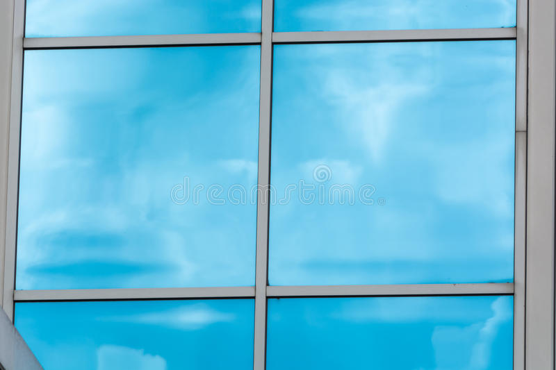 Glass building facade with reflections. Beautiful glass building facade with reflections from a blue sky and cloud formations royalty free stock images