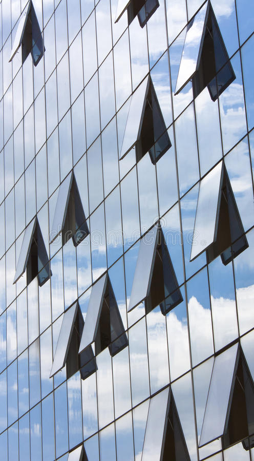 Glass building reflecting clouds. Sky and clouds reflecting on the modern glass building with some windows opened stock image