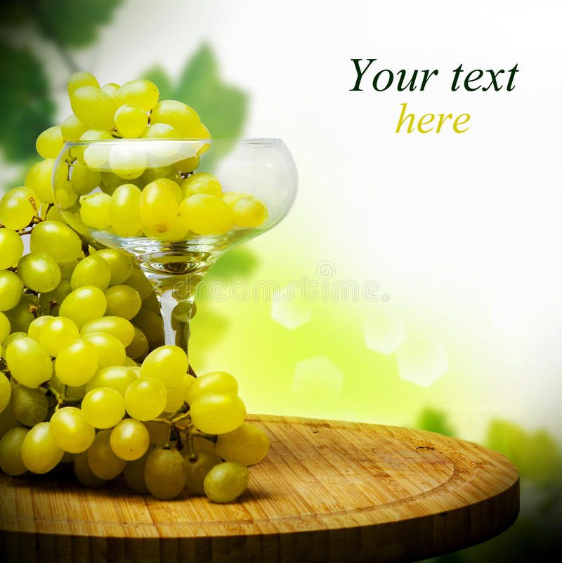 Glass with Bunch of ripe grapes stock photo