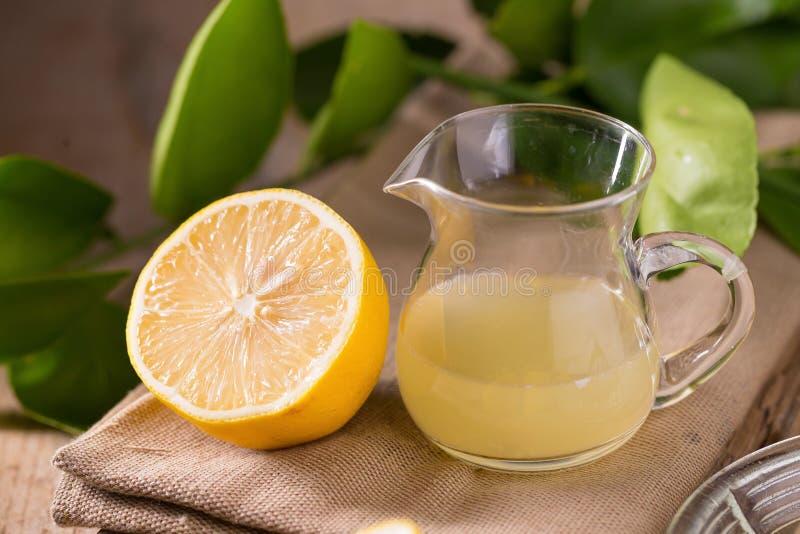 glass bunke av nytt sammanpressat citronjuice, citronpress och r royaltyfri bild