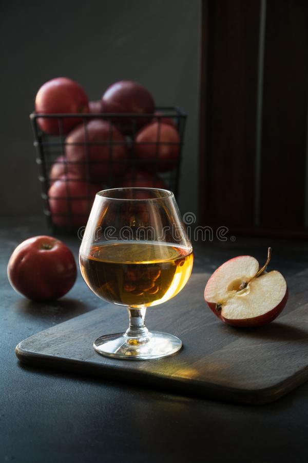 Glass with Calvados brandy and red apples on black. royalty free stock photos