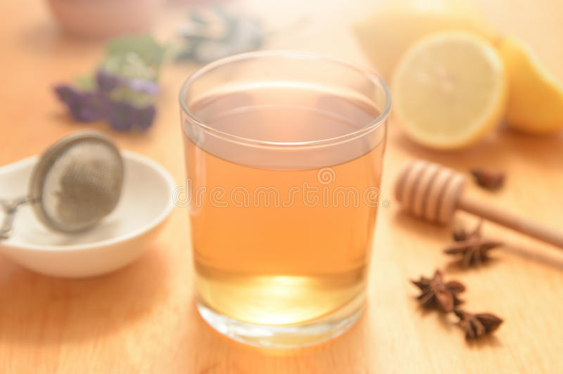 A glass of camomile with some natural honey and anise seeds stock photography
