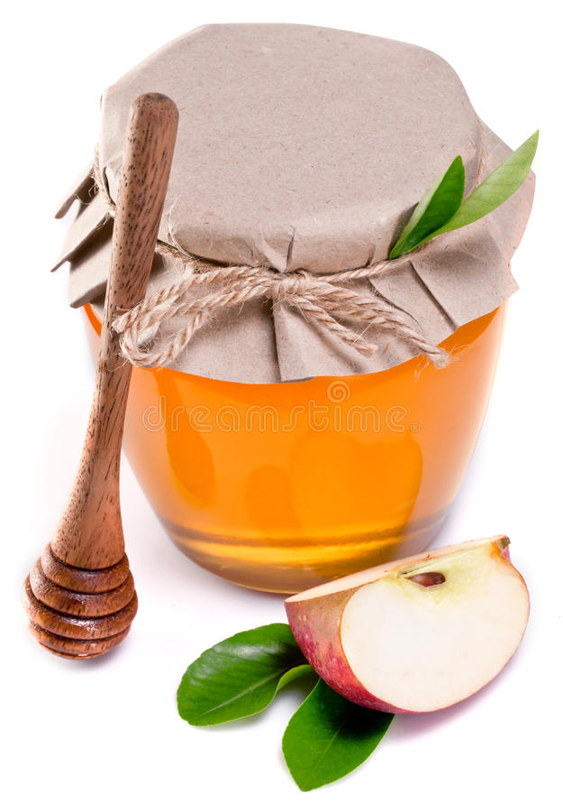 Glass can full of honey. Glass can full of honey, piece of apple and wooden dripper over white royalty free stock photo