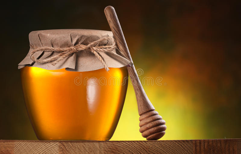 Glass can full of honey and wooden dripper. Glass can full of honey and wooden dripper on brown background stock photos
