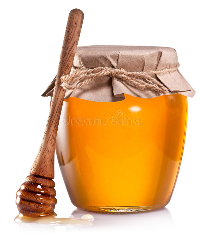 Glass can full of honey and wooden dripper on a white. Glass can full of honey and wooden dripper on a white background stock image