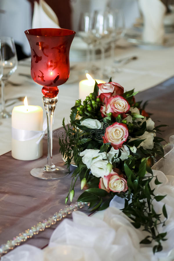 Glass, candles and flowers royalty free stock photography