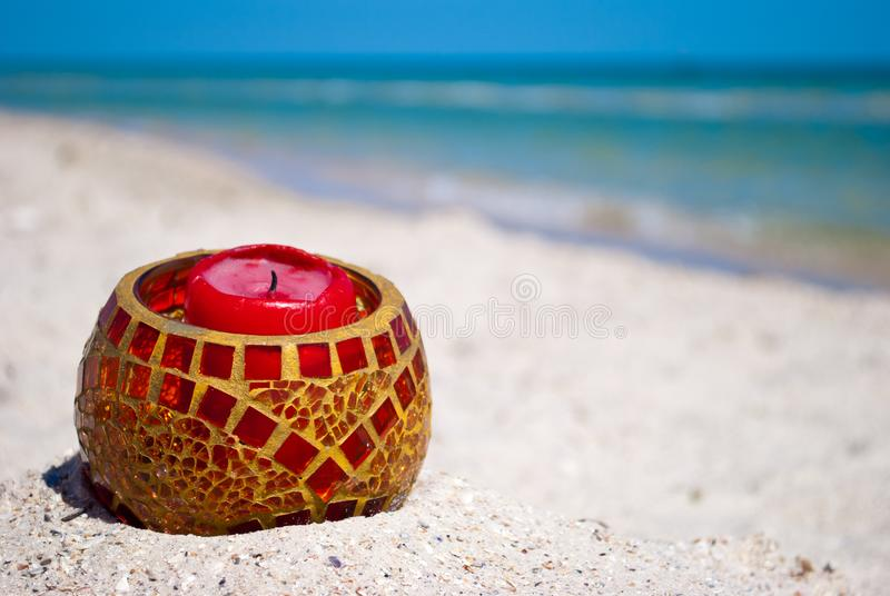 Glass candlestick and a red candle on the sand on a background of blue sea and blue sky royalty free stock photo