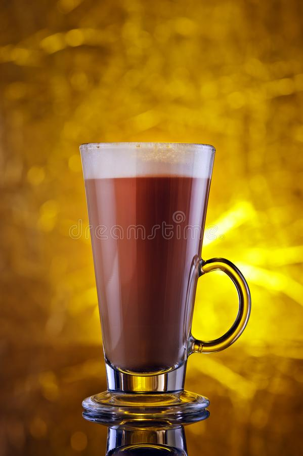 A glass of cappuccino on a black table royalty free stock photo