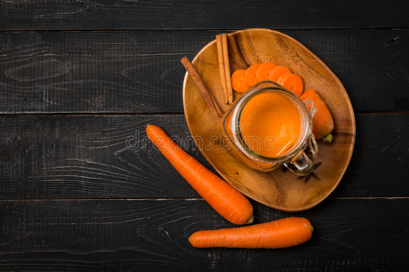 Glass of carrot juice and carrots royalty free stock photography
