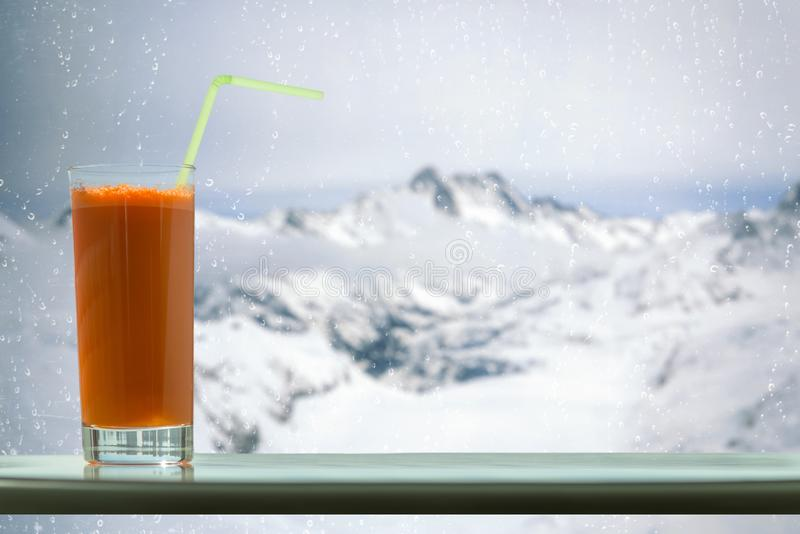 A glass of carrot juice with a straw in the cafe on the Aletsch glacier background in Switzerland stock photos