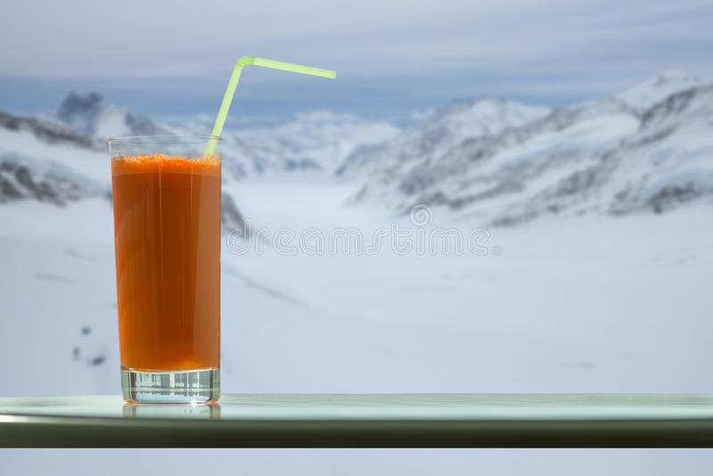 A glass of carrot juice with a straw in the cafe on the Aletsch glacier background in Switzerland royalty free stock photography