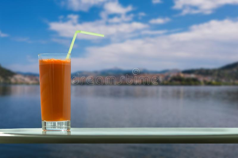 A glass of carrot juice with a straw in the cafe on the background of a distant city of Kastoria and Orestias lake stock photography