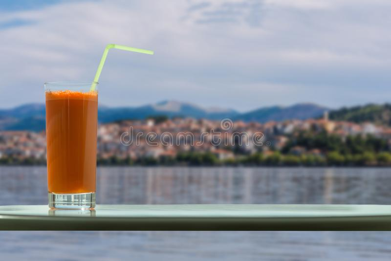 A glass of carrot juice with a straw in the cafe on the background of Kastoria city and Orestias lake royalty free stock photos