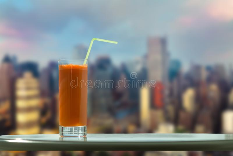 A glass of carrot juice with a straw in the cafe on the background Manhattan. New York City stock photos