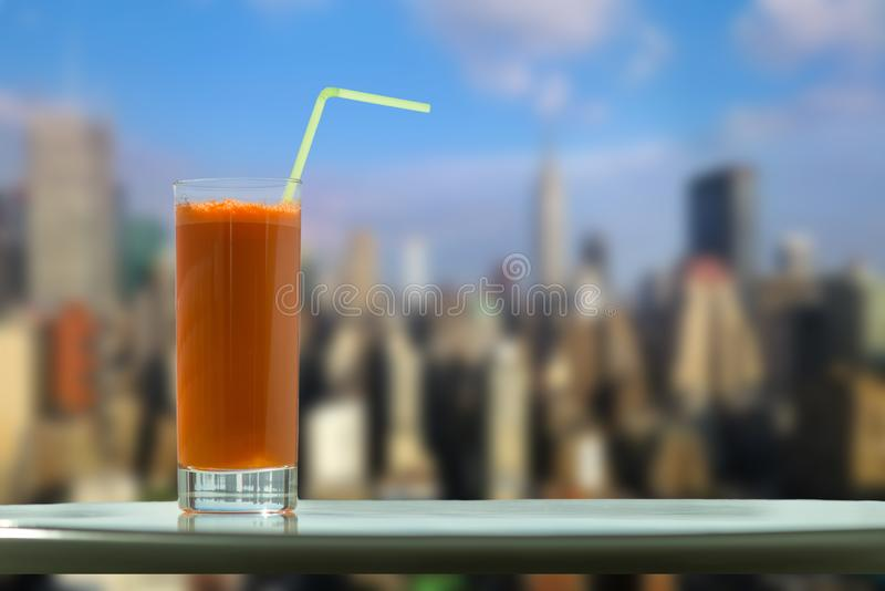A glass of carrot juice with a straw in the cafe on the Manhattan skyscrapers background royalty free stock photo