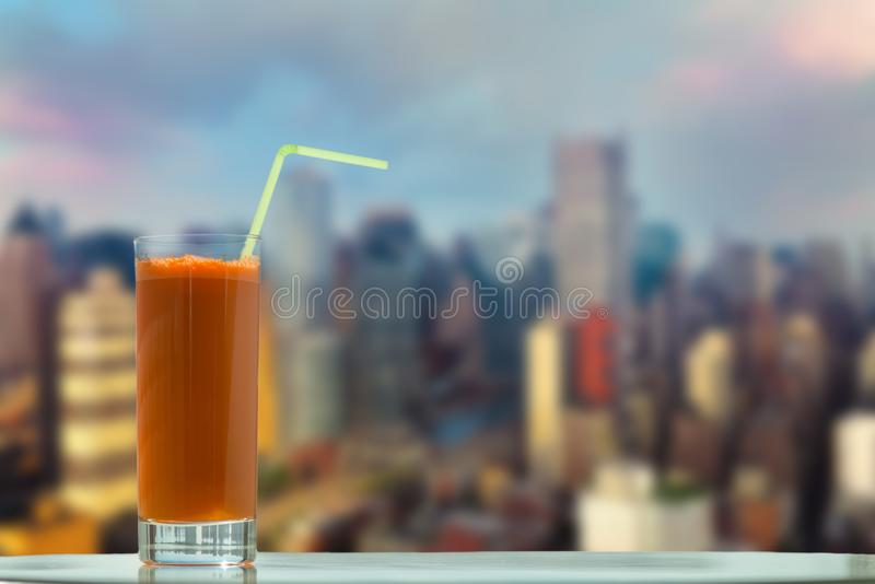 A glass of carrot juice with a straw in the cafe on the Manhattan skyscrapers background royalty free stock images