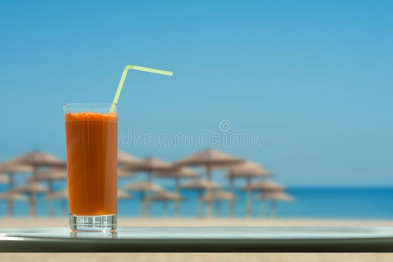 A glass of carrot juice with a straw in the cafe on the beach and straw umbrellas backgrounds stock images
