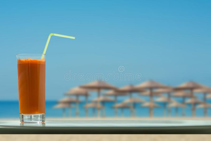 A glass of carrot juice with a straw in the cafe on the tropical beach backgrounds royalty free stock photography