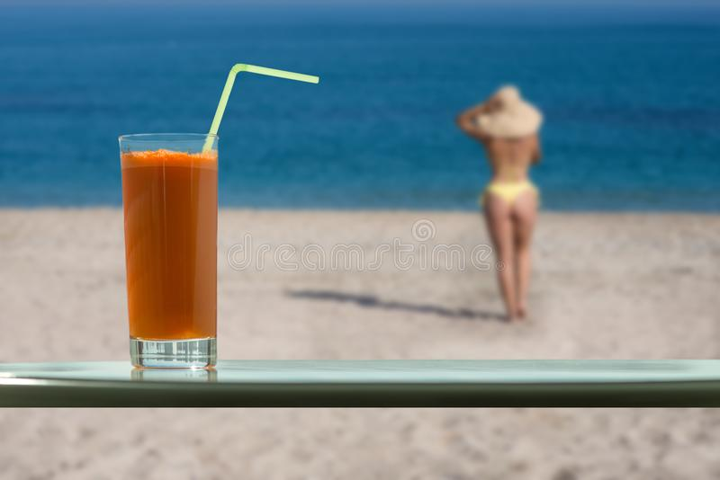 A glass of carrot juice with a straw in the cafe. Female in the bikini and straw hat on the beach stock image