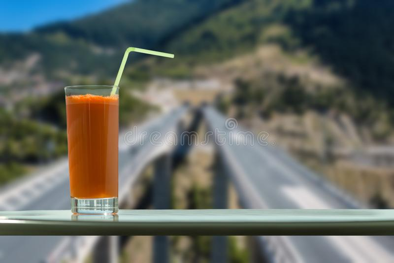 A glass of carrot juice in the cafe with view on a speed highway through the window stock photos