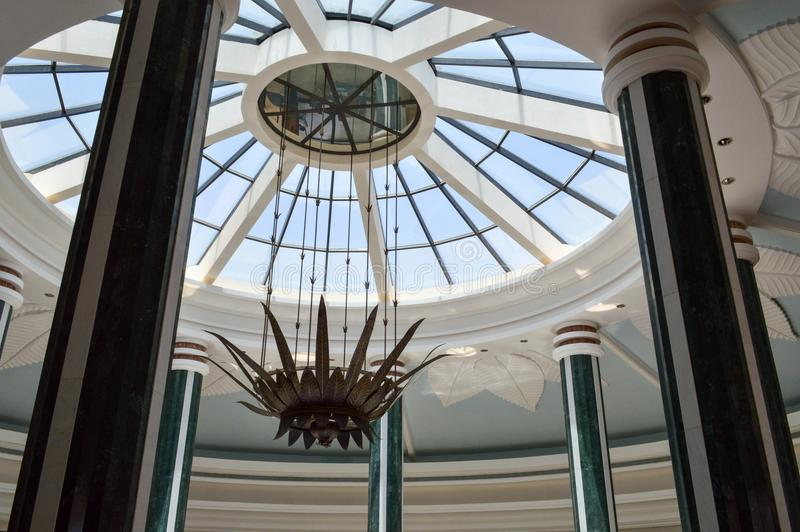 Glass ceiling dome round roof windows sky decorations stone leaves flowers ceiling decorative plaster large columns background. View of the glass ceiling dome of stock images