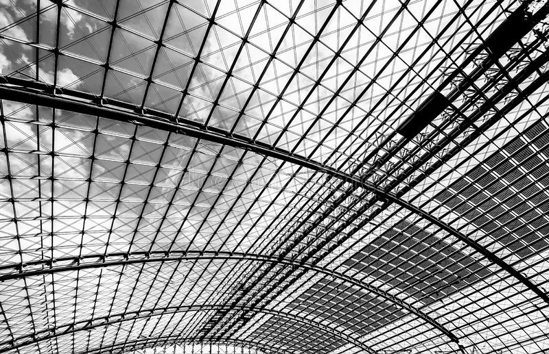 Glass ceiling on a sunny day. Berlin, Germany, August 18, 2018. Glass ceiling on a sunny day at the central railway station in Berlin uncolored, black and white royalty free stock images