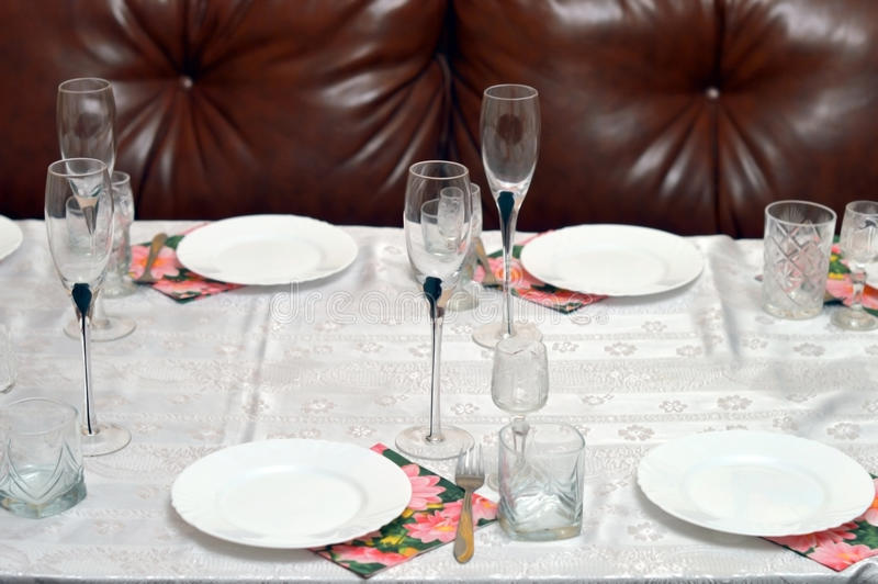 Glass and ceramic ware on a table. Against a leather sofa stock photos