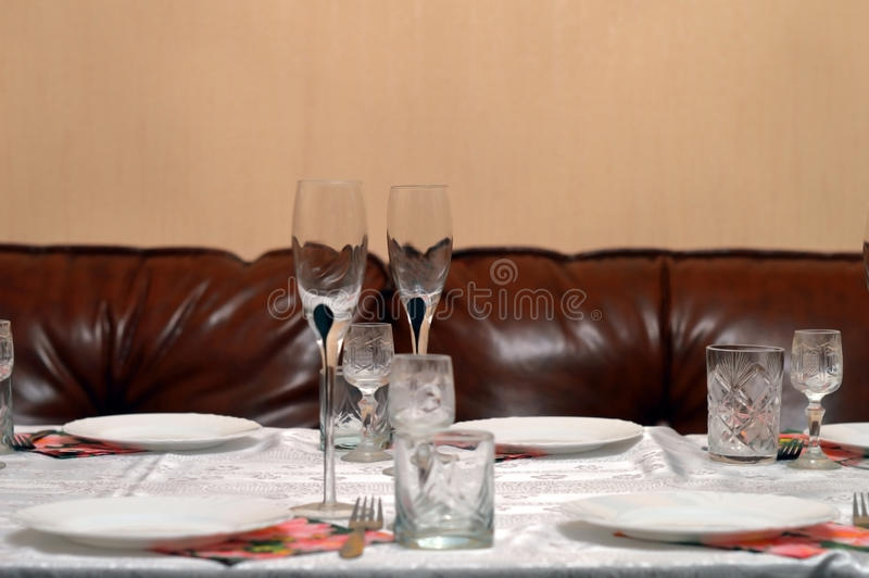 Glass and ceramic ware on a table. Against a leather sofa stock photo