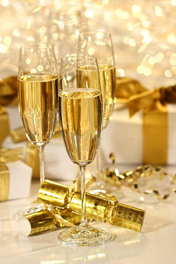 Glass of champagne against sparkle background. Glass of champagne against gold sparkle background royalty free stock photo