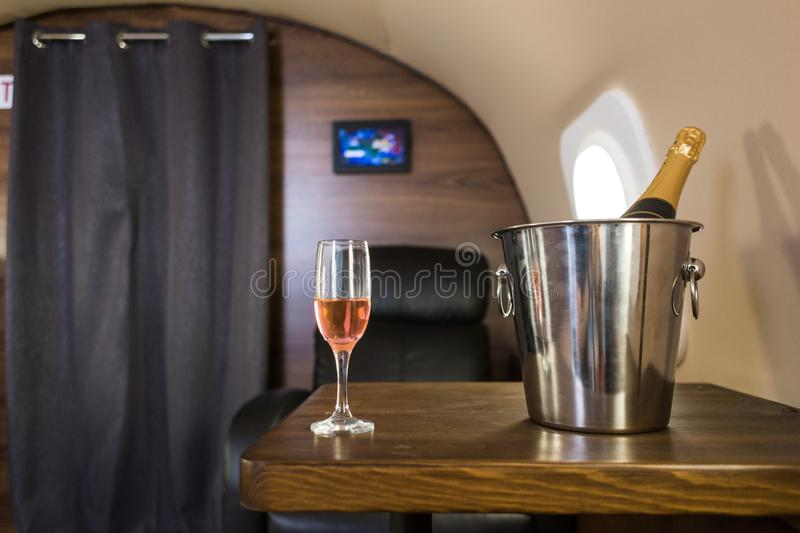 A glass of champagne in the interior of a private jet. Flying first class.  stock photo